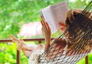 9912221-young-woman-lying-in-hammock-in-a-garden-and-reading-a-book-shallow-dof-focus-on-a-left-shoulder