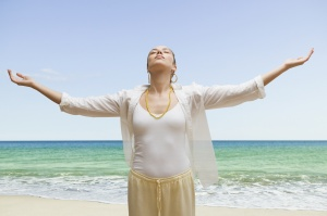 Woman at beach with arms outstretched