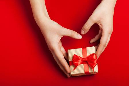 82523813-hands-holding-gift-in-kraft-box-on-a-red-background-the-concept-of-st-valentine-s-day-weddings-engag